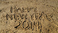 Happy new year words written in sand the on the beach Stock Photos