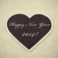 Happy new year written in a heart shaped blackboard on a vintage background with a retro effect Royalty Free Stock Image