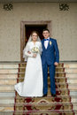Happy newly married couple posing on stairs at hall big Stock Photos