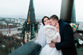 Happy newlywed bride and groom have a sweet ardent moment on the balcony of old gothic cathedral Royalty Free Stock Photo