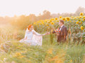 Happy newlywed couple at their wedding day in the sunflower field on sunset. Royalty Free Stock Photo