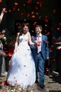 Happy newlyweds and flying red petals Royalty Free Stock Photo
