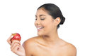 Happy nude brunette holding red apple on white background Royalty Free Stock Photos