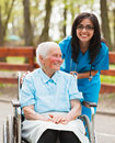 Happy nurse with happy patient smiling elderly lady and in park enjoying their time together Royalty Free Stock Photo