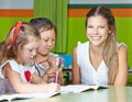 Happy nursery teacher with kids drawing in a kindergarten Royalty Free Stock Photography