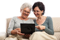 Happy old and adult women with small notebook people laptop browsing internet pointing at computer screen looking isolated on Royalty Free Stock Images