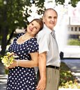 Happy old couple with flower back to backoutdoor Royalty Free Stock Photography
