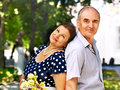 Happy old couple with flower back to backoutdoor Stock Images