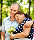 Happy old couple with flower outdoor Stock Photography