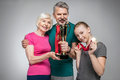 Happy old couple and girl holding sport trophy and medals