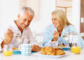Happy old couple having breakfast at the table Royalty Free Stock Photo