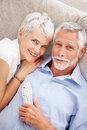 Happy old couple holding a remote control Royalty Free Stock Photos