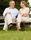 Happy old couple sitting on a bench at the park Stock Photo