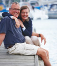 Happy old couple standing together at harbor Royalty Free Stock Images