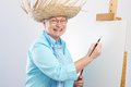 Happy old lady with canvas and paintbrush Royalty Free Stock Photo