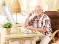 Happy old man on landline call sitting at desk using computer smiling looking at camera Stock Images