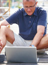 Happy old man sitting on quay using laptop Stock Photo