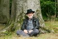 Happy old man sitting under tree in the forest Royalty Free Stock Photo