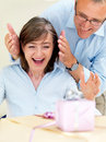 Happy old man surprising his wife with gifts Royalty Free Stock Photography