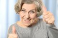 Happy old woman beautiful showing thumbs up on a blue background Stock Photography