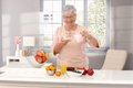 Happy old woman eating healthy preparing breakfast pouring milk over cereals smiling looking at camera Stock Photography