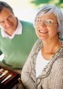 Happy old woman with a man at the background Stock Photo
