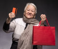Happy old woman with shopping bags and credit card on a gray background Royalty Free Stock Images
