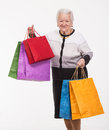 Happy old woman with shopping bags on a white background Royalty Free Stock Photography