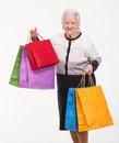 Happy old woman with shopping bags on a white background Royalty Free Stock Photos