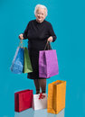 Happy old woman with shopping bags on a white background Royalty Free Stock Photo