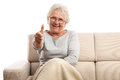 Happy old woman thumb up copy space sitting on the sofa and gesturing thumbs blanket on feet isolated on white background Royalty Free Stock Photography