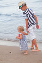 Happy older brother and younger cute sister walking on sea coast italy Stock Images