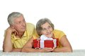 Happy older couple with gift portrait of a spending time together Stock Photos