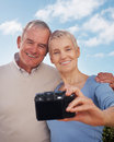 Happy older couple smiling with a camera Stock Image