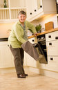 Happy older woman is designer kitchen Royalty Free Stock Photo