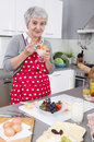 Happy older woman preparing breakfast and eating yogurt wearing a red kitchen apron Stock Images