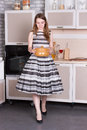 Happy ordinary woman with pan at her kitchen Stock Images