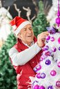 Happy owner decorating christmas tree in santa hat at store Stock Images