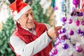 Happy owner decorating christmas tree at store male in santa hat Stock Photos