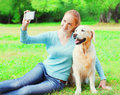 Happy owner woman with Golden Retriever dog is taking picture selfie portrait on a smartphone on summer day Royalty Free Stock Photo