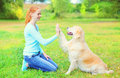 Happy owner woman training Golden Retriever dog on grass Royalty Free Stock Photo
