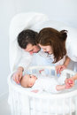 Happy parent looking at their baby son in round crib young parents cute smiling a white Stock Photos