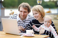 Happy parenthood young parents with their sweet baby girl in outdoors cafe Stock Images