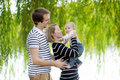 Happy parenthood young parents with their sweet baby girl in sunny park Stock Photography