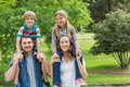 Happy parents carrying kids on shoulders at park portrait of the Royalty Free Stock Photography