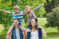Happy parents carrying kids on shoulders at park portrait of the Royalty Free Stock Images