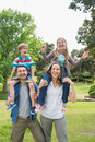 Happy parents carrying kids on shoulders at park portrait of the Royalty Free Stock Image