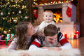 Happy parents and child play near Christmas tree at home. Father, mother and son celebrating New Year together Royalty Free Stock Photo