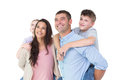 Happy parents giving piggyback ride to children while looking up Royalty Free Stock Photo