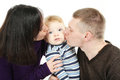 Happy parents kissing their child Stock Photo